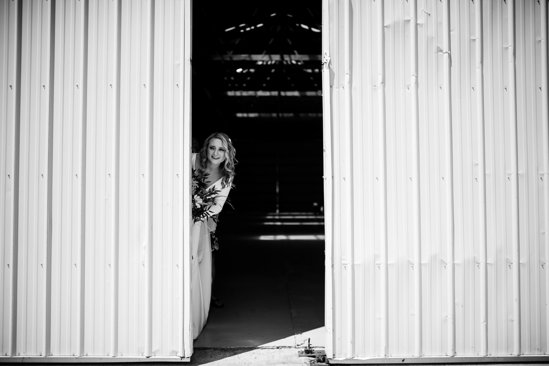 bride peaking out from barn