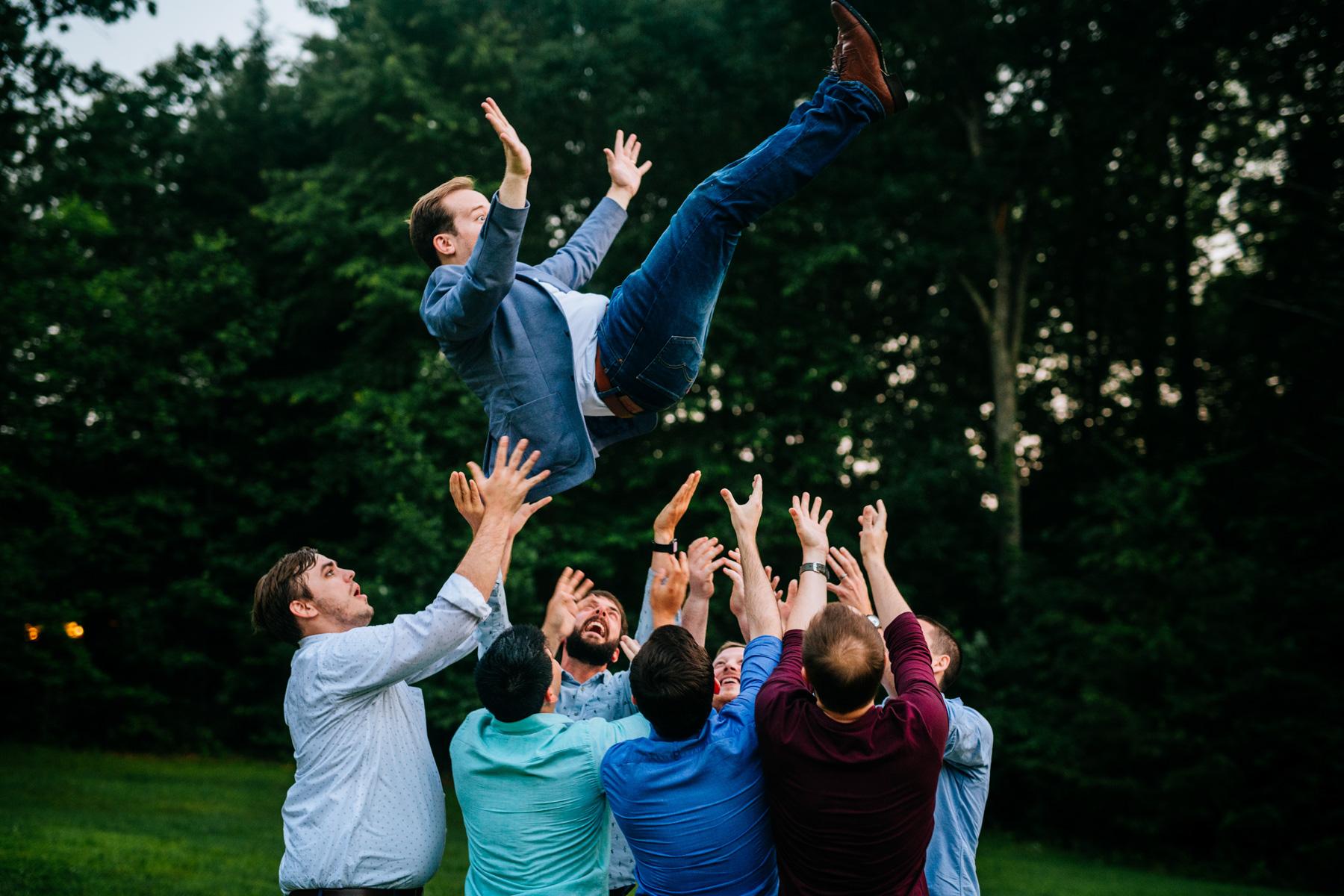 groom getting tossed in air