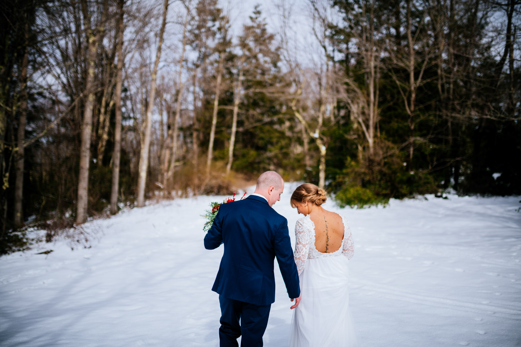bride and groom walking through snow