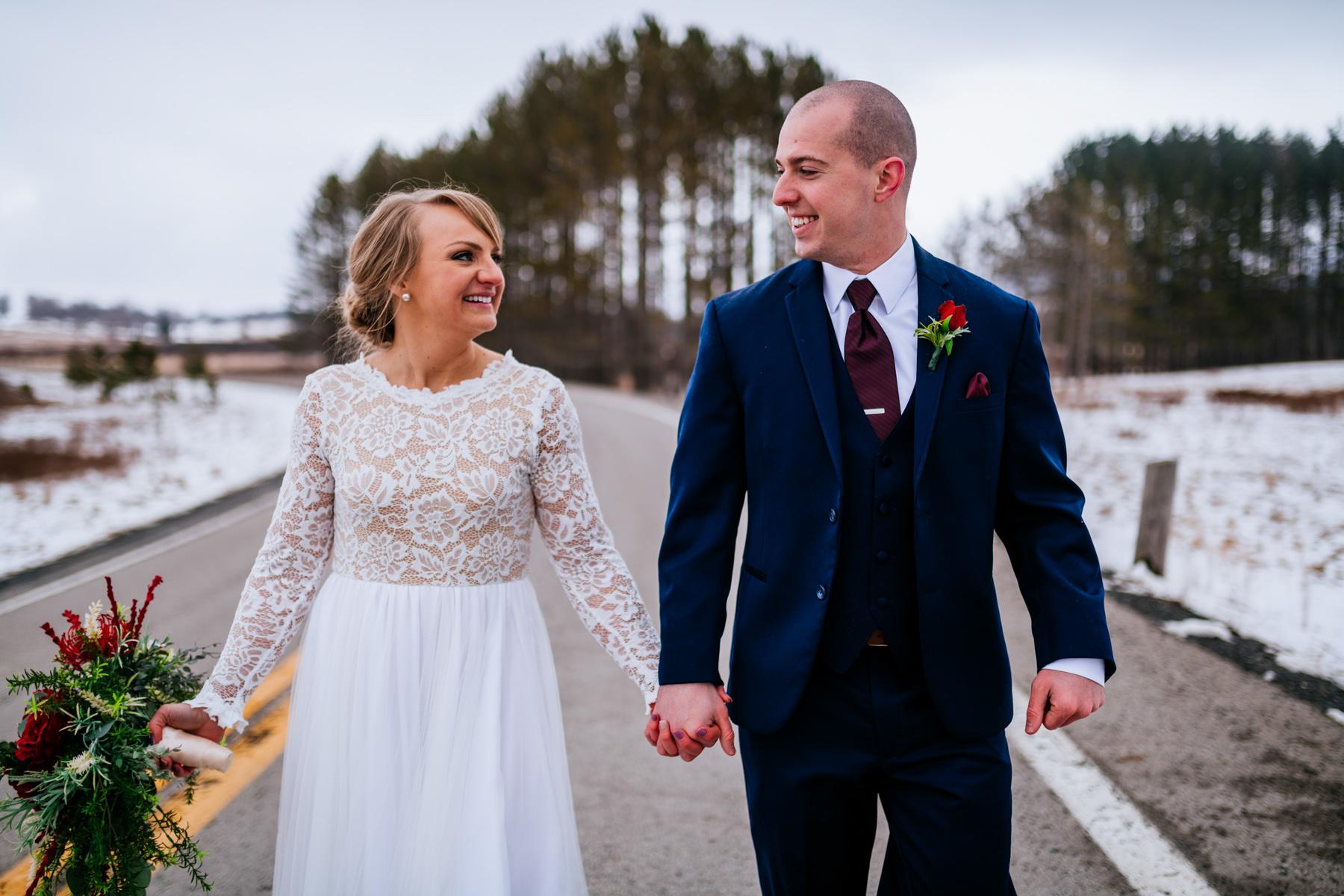 wedding couple strolling down road in winter