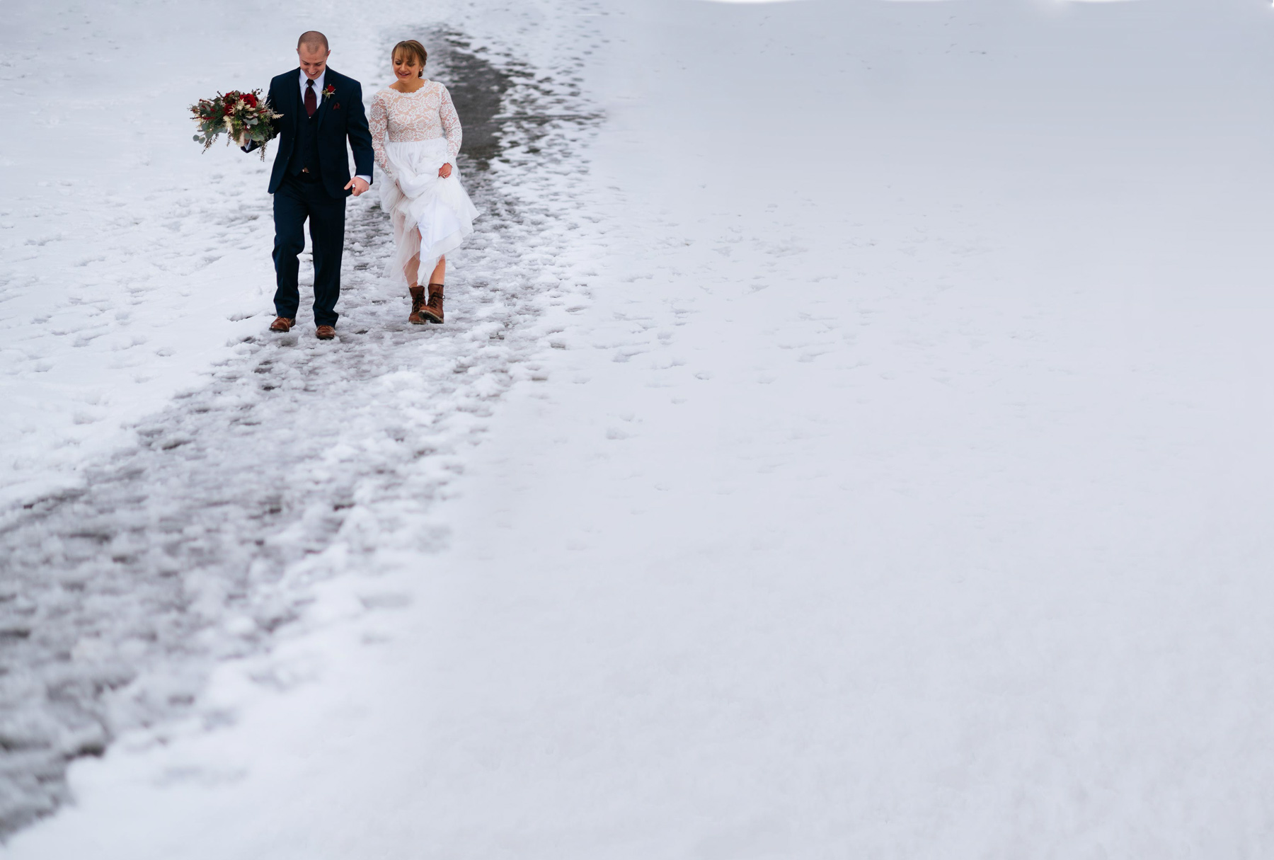bride and groom walk through snow pendleton point wedding