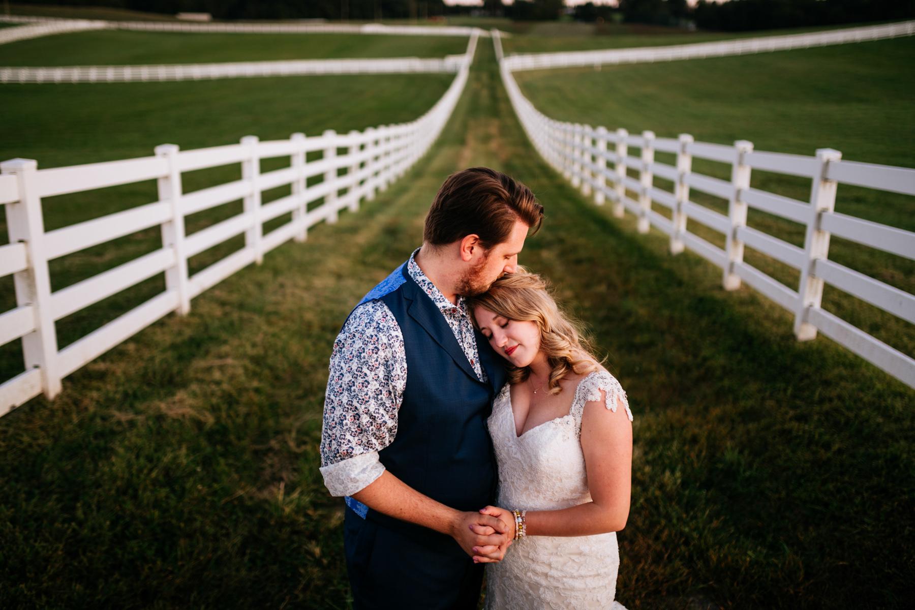 groom kisses brides head vignon manor farm wedding