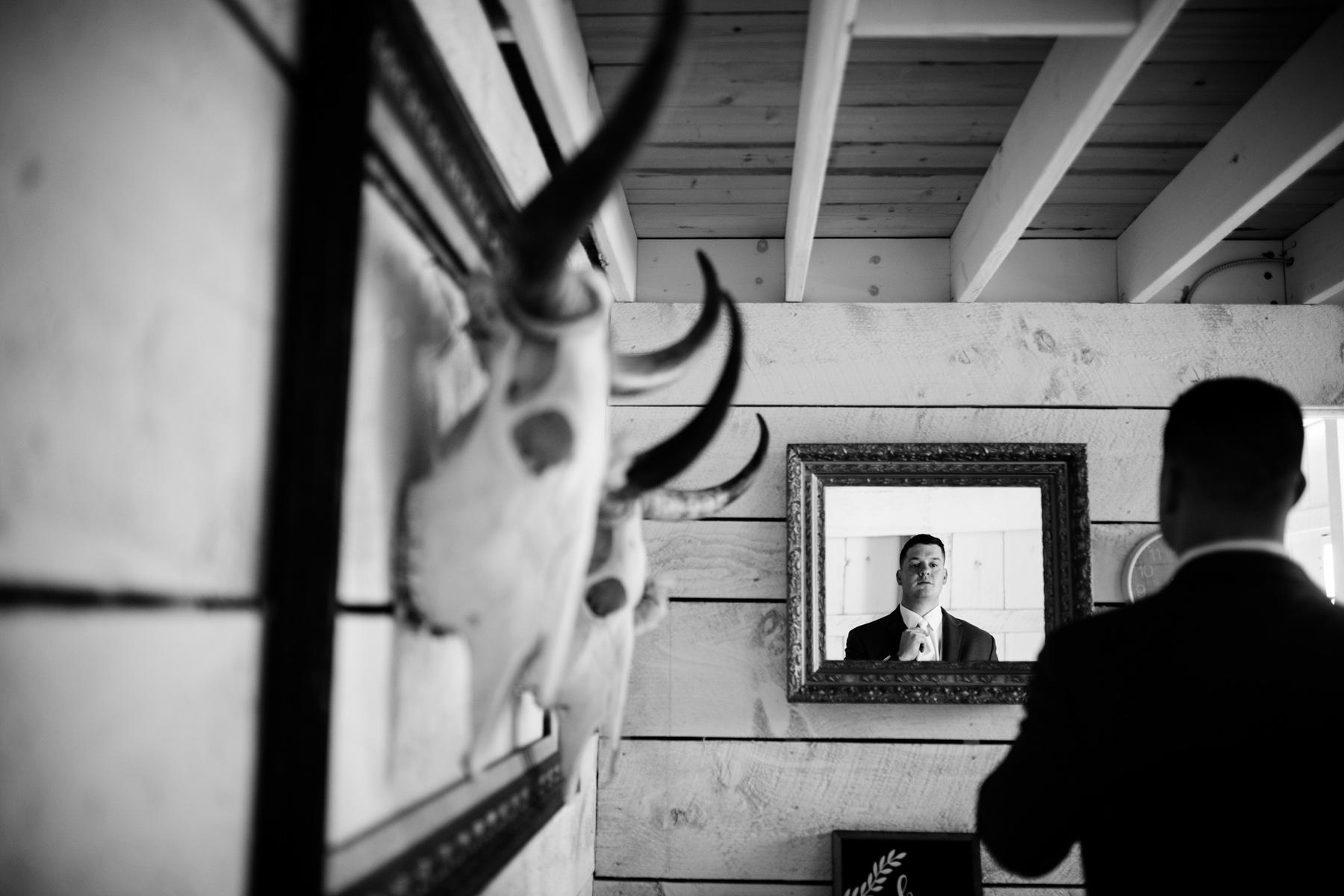 groom gets dressed white barn at lucas farm wedding