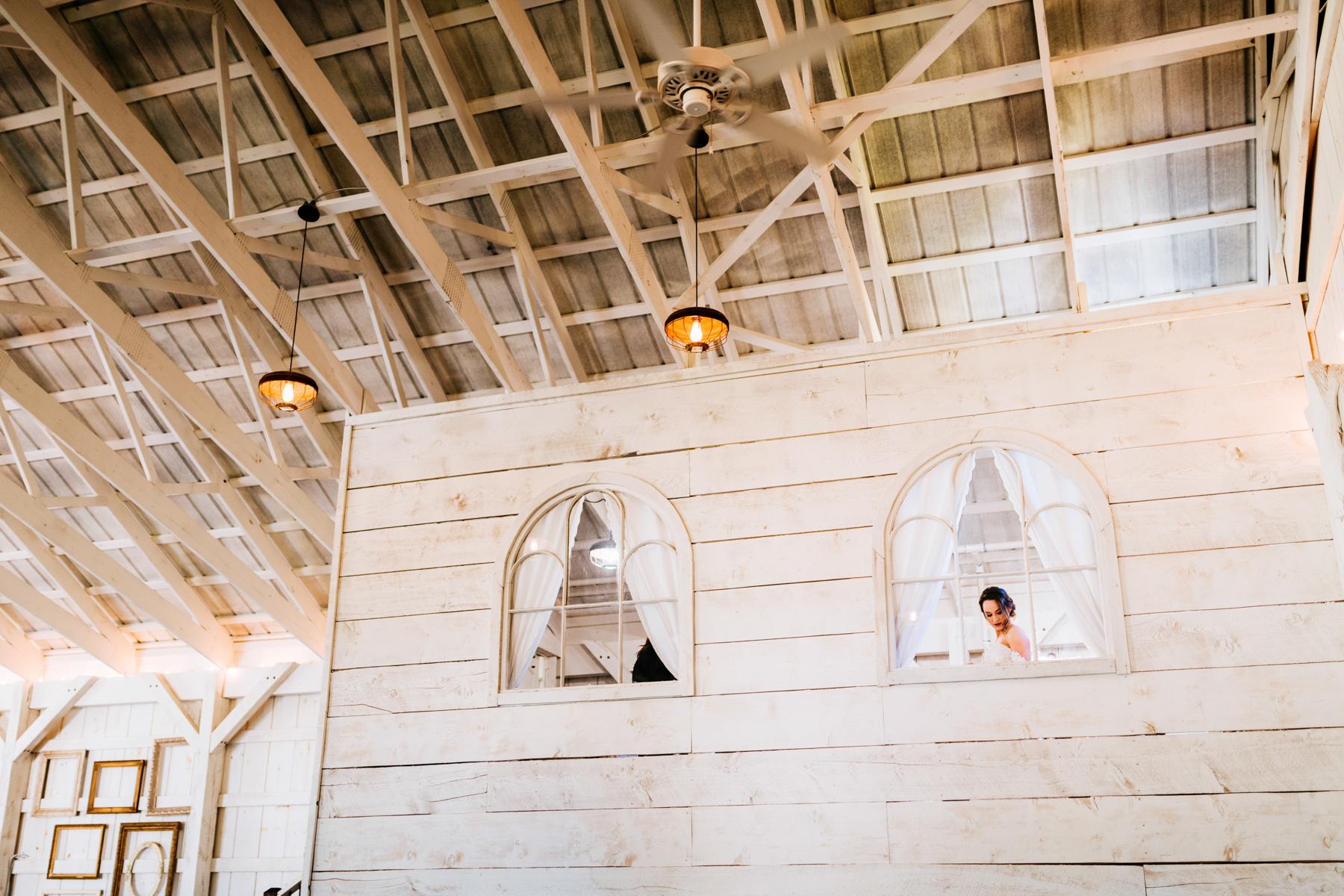 bride getting dressed at white barn at lucas farm wedding