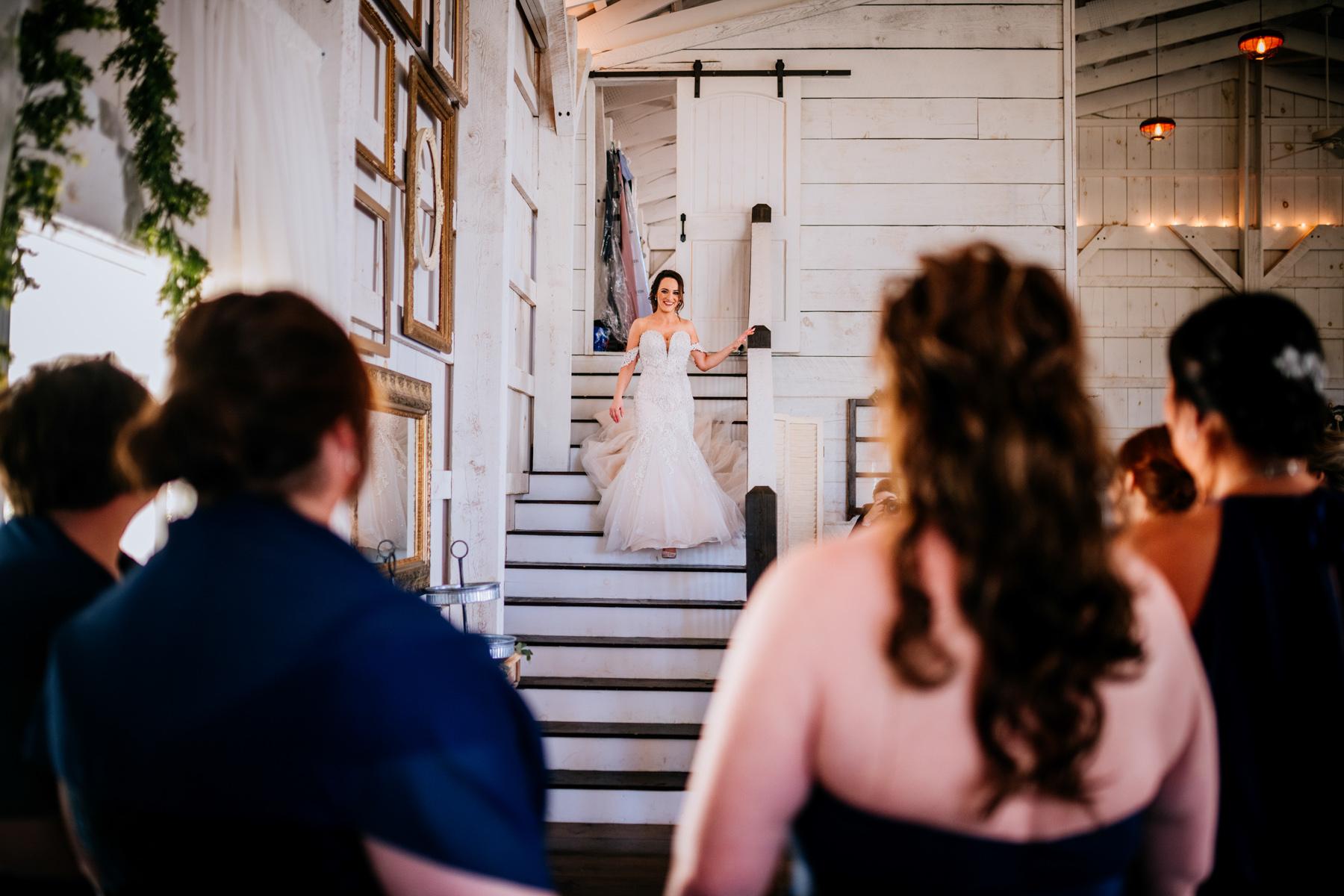 bride descends stairs white barn at lucas farm wedding