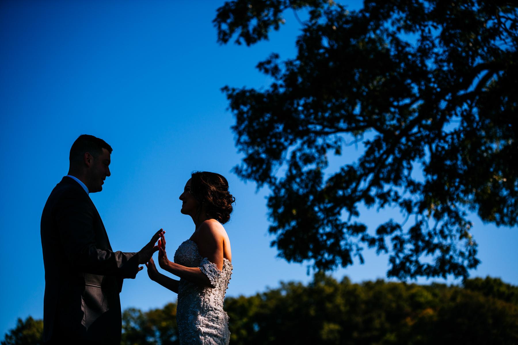 bride seeing groom in silhouette white barn at lucas farm wedding