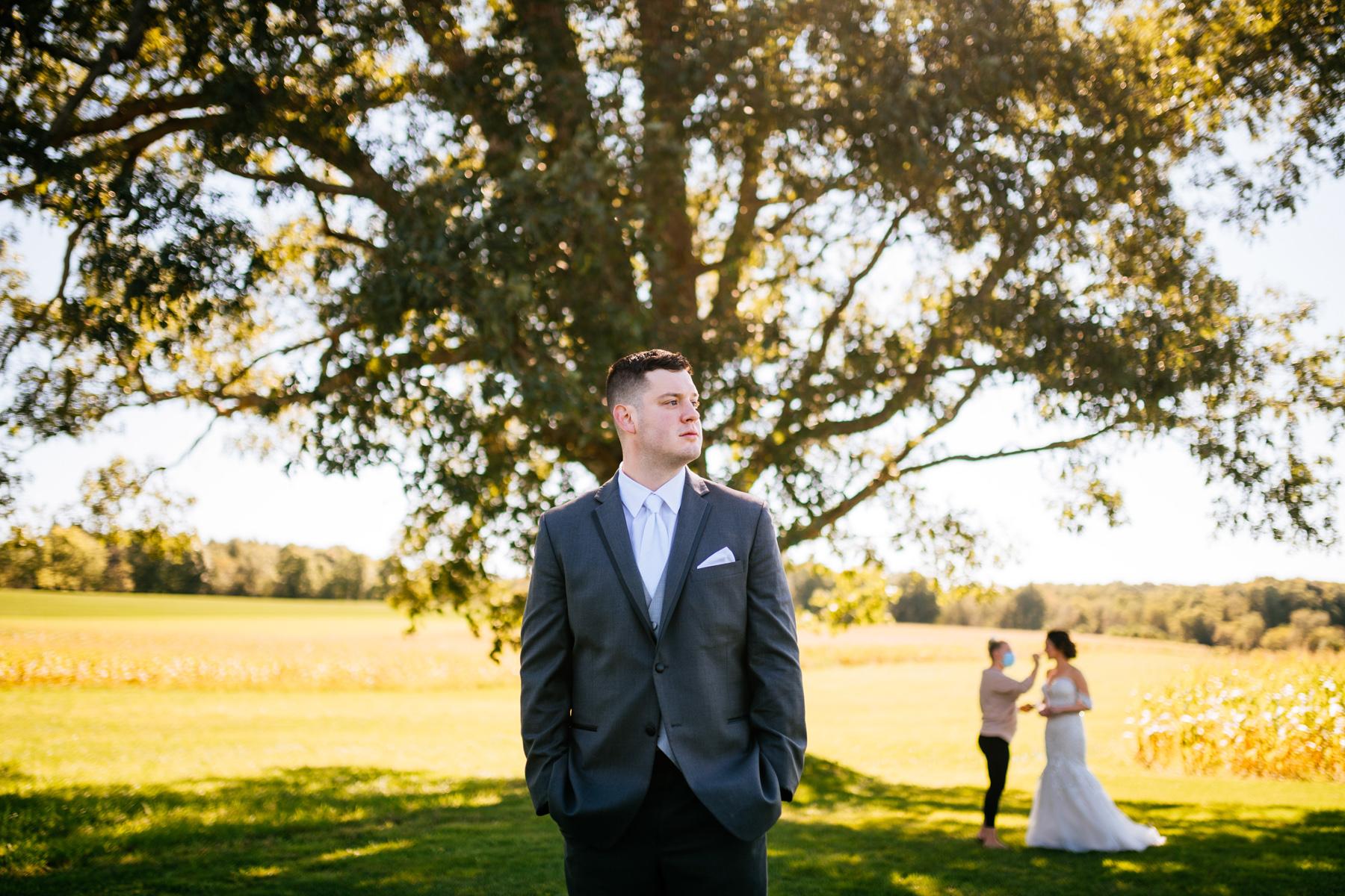 groom in front of oak tree