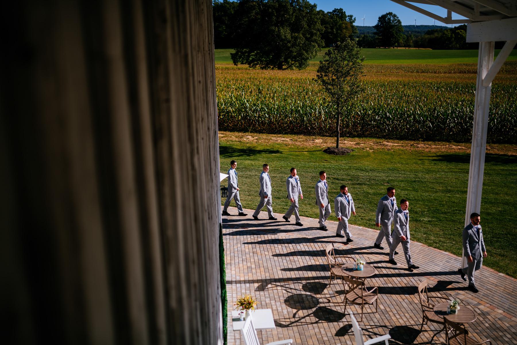 groomsmen entering ceremony white barn at lucas farm wedding