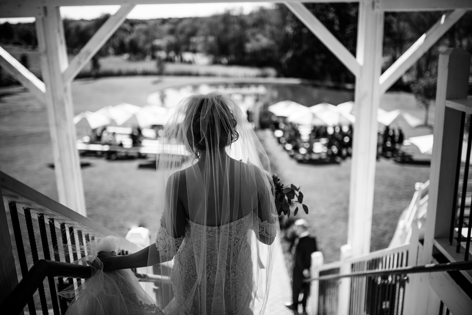 bride descending stairs at white barn at lucas farm wedding