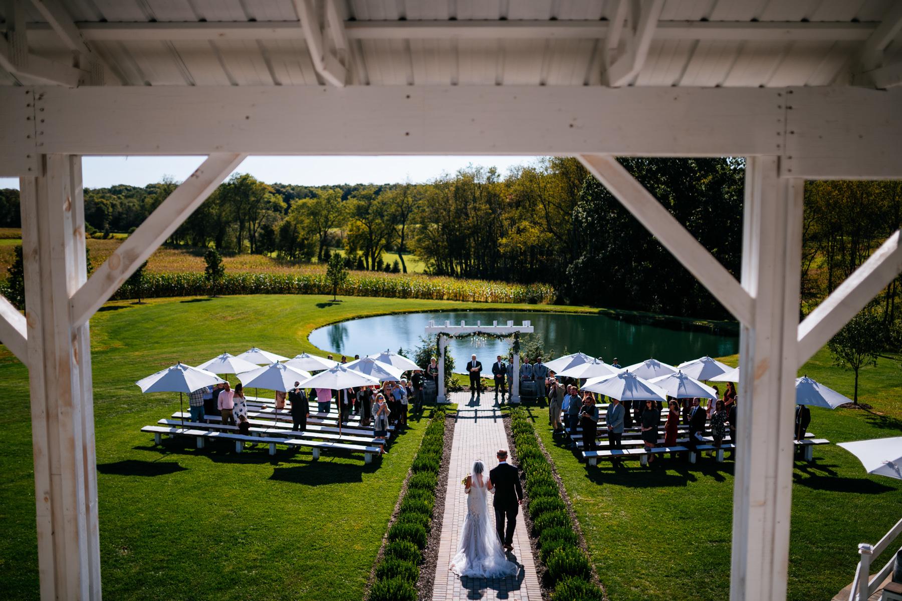 bride and dad walk down aisle white barn at lucas farm wedding