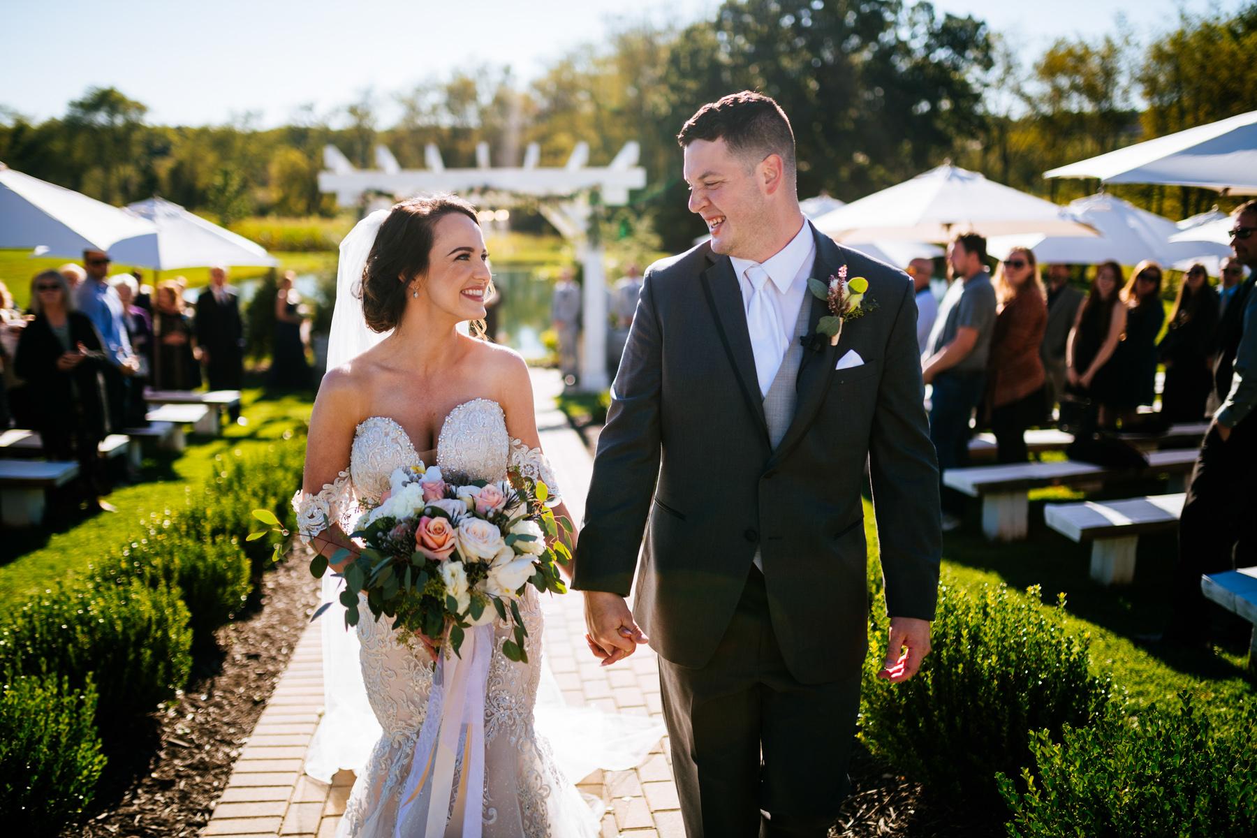 couple exits ceremony white barn at lucas farm wedding