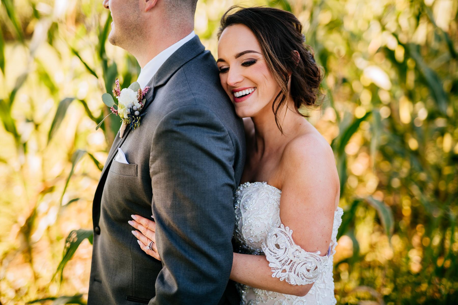 happy bride hugs groom from behind