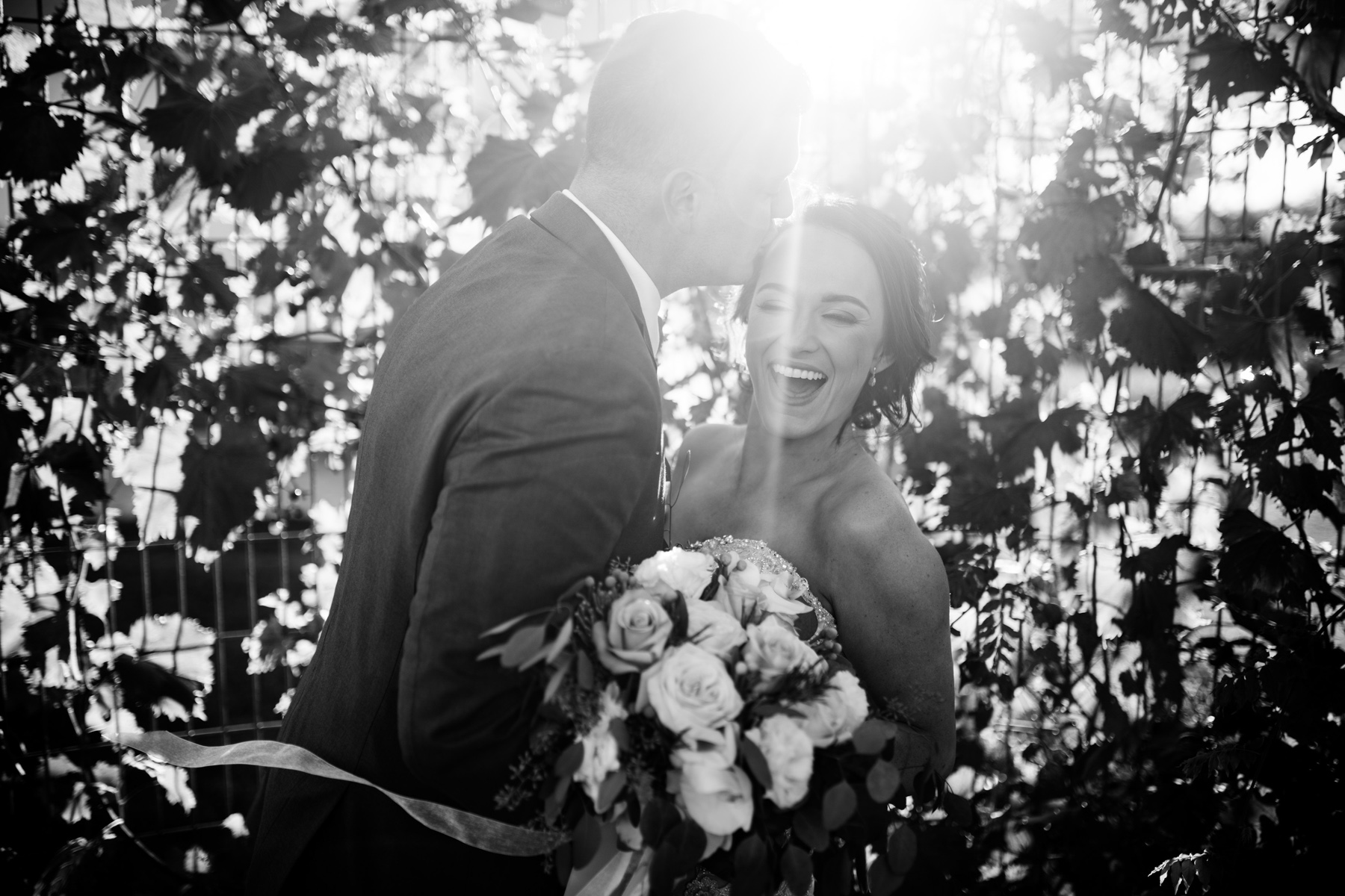 groom kisses bride while she laughs with flare