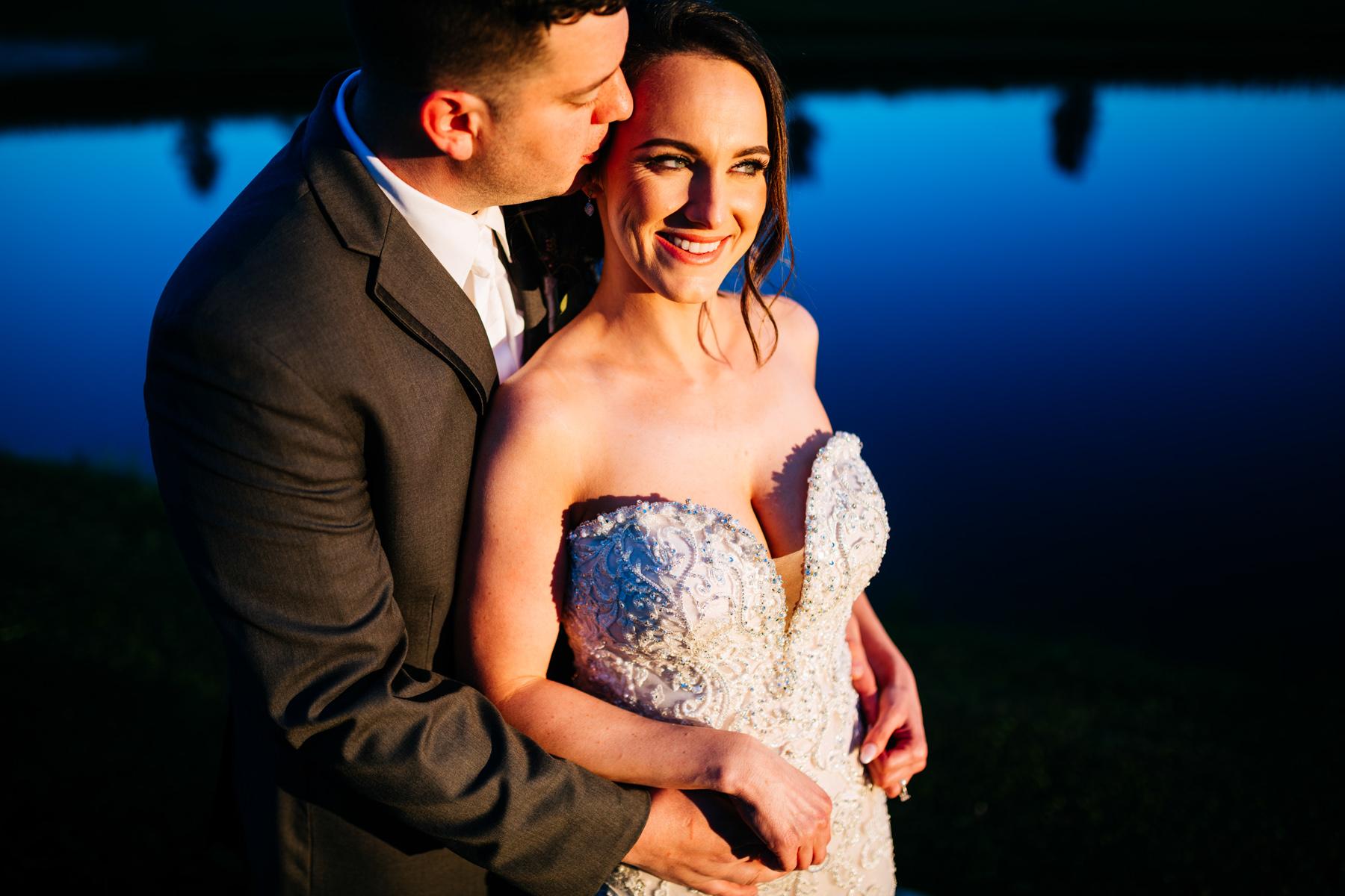 groom hugs bride in front of lake