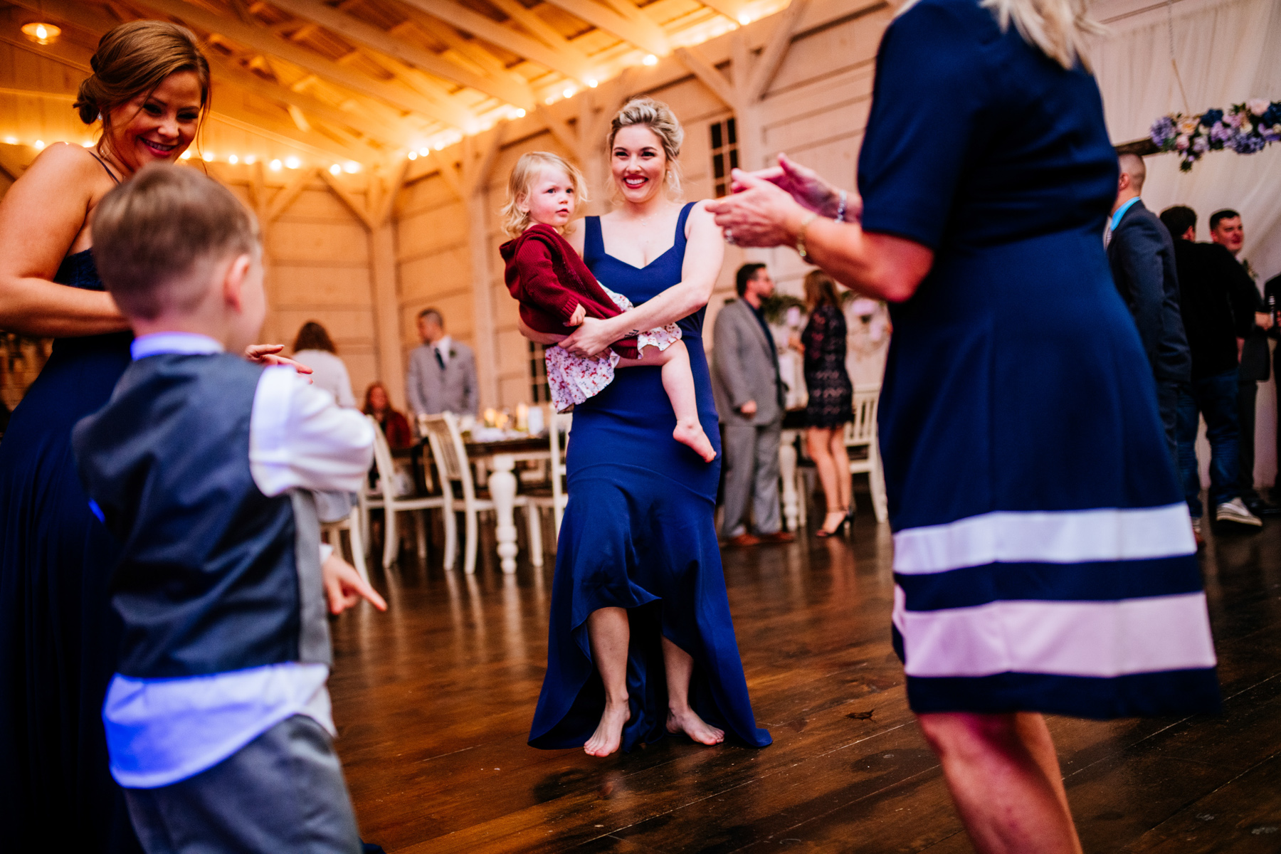 woman dances with child during wedding reception