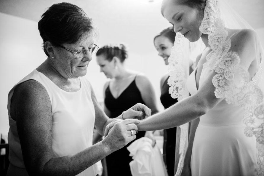 mom puts bracelet on bride
