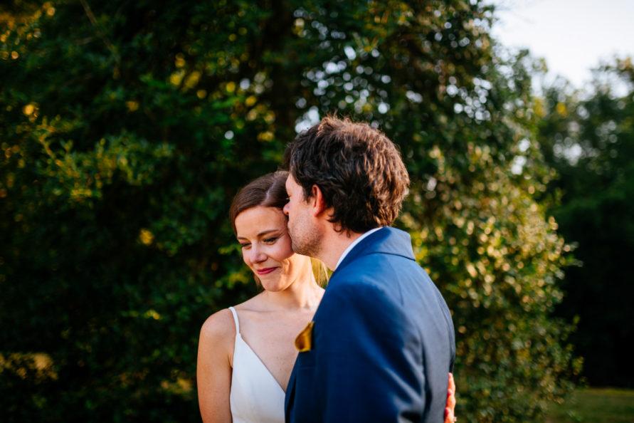 groom kisses brides head