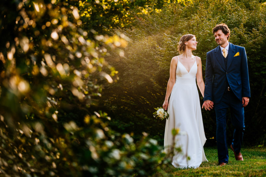 bride and groom walking amongst trees