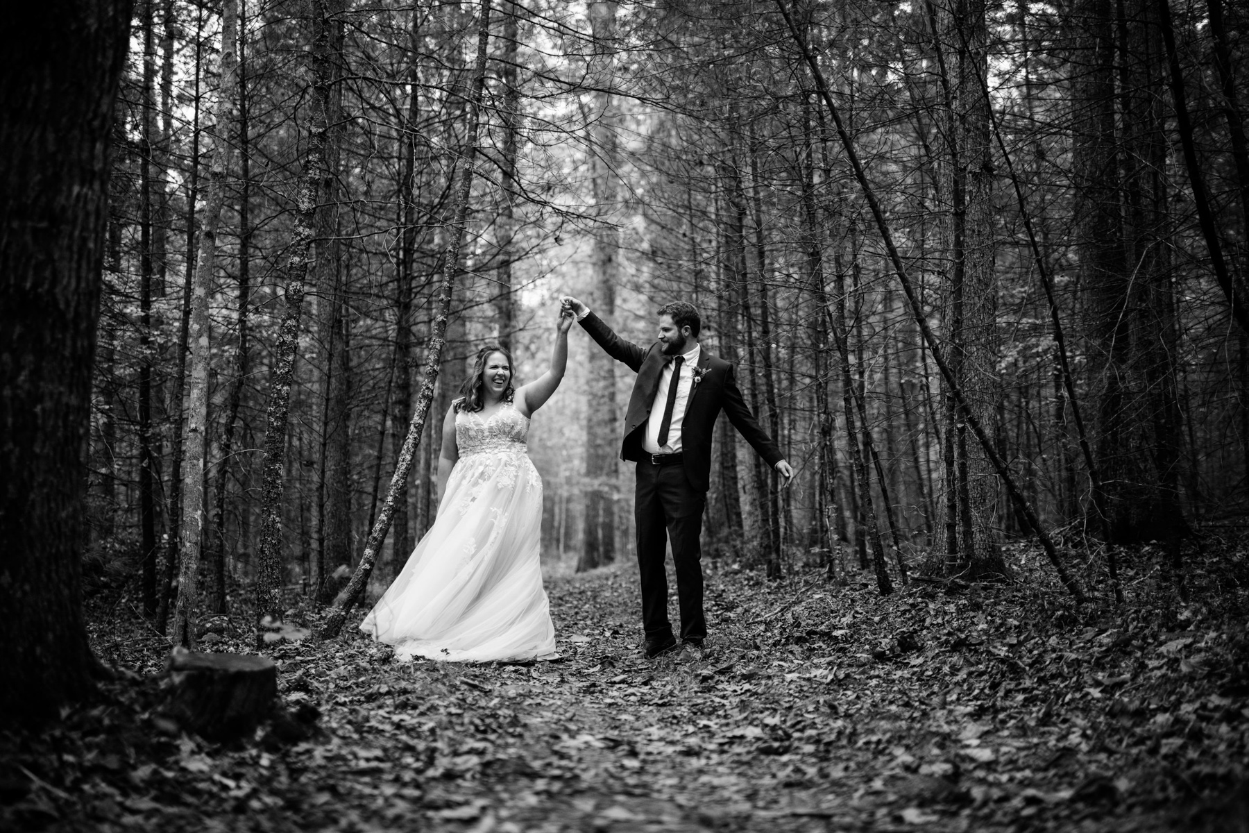 groom spins bride in forest