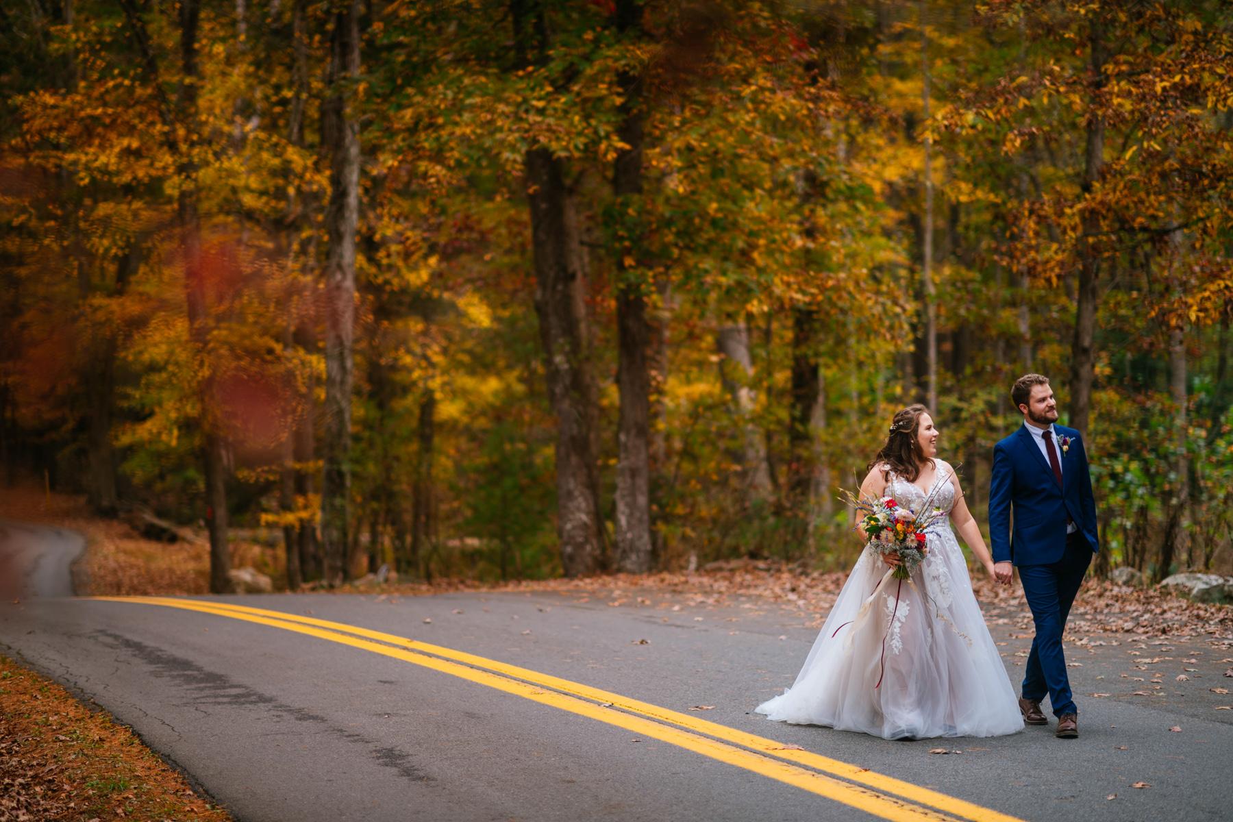 bride groom walking down wv road in fall